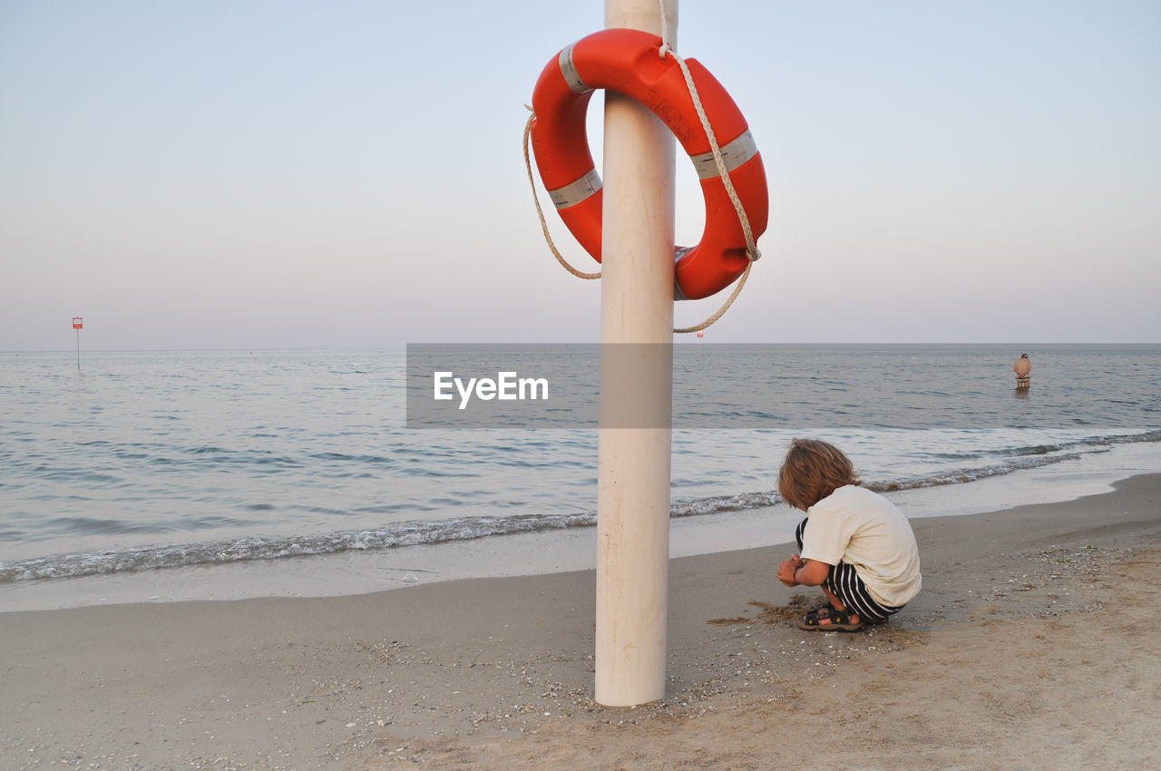 Rear view of boy playing at shore by lifebelt on pole against sky