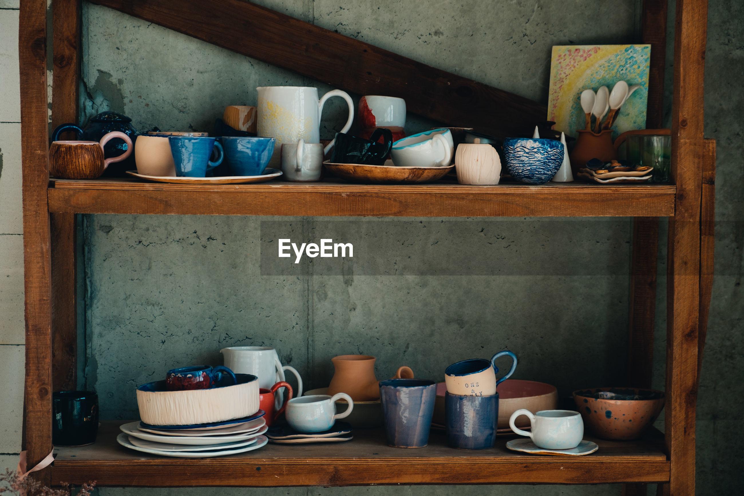 Kitchen utensils in shelf at home