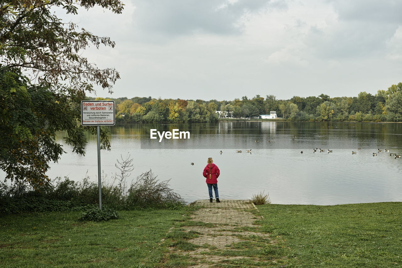 Rear view of woman overlooking calm lake