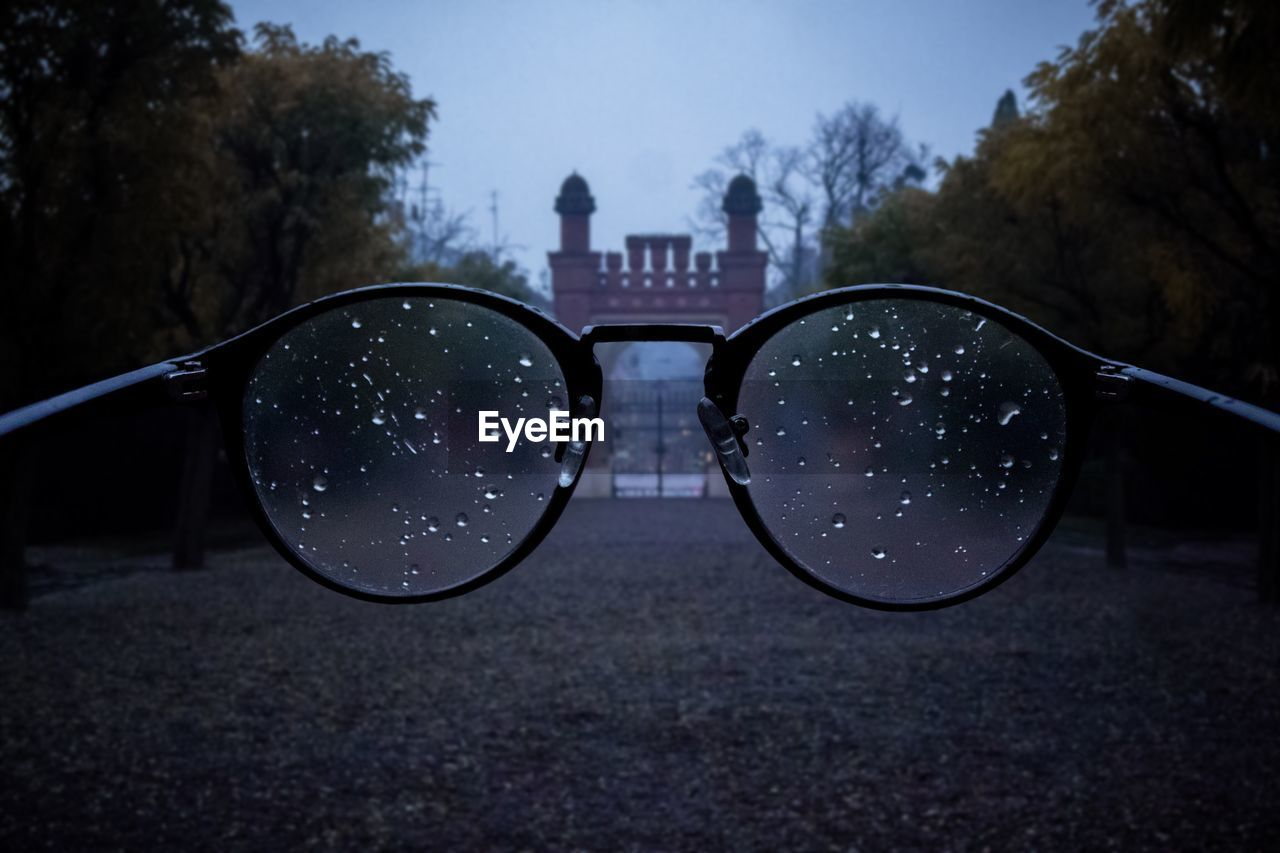 glasses, focus on foreground, eyeglasses, nature, transparent, close-up, personal accessory, built structure, no people, tree, sky, glass - material, outdoors, day, reflection, wet, architecture, eyesight, building exterior, eyewear
