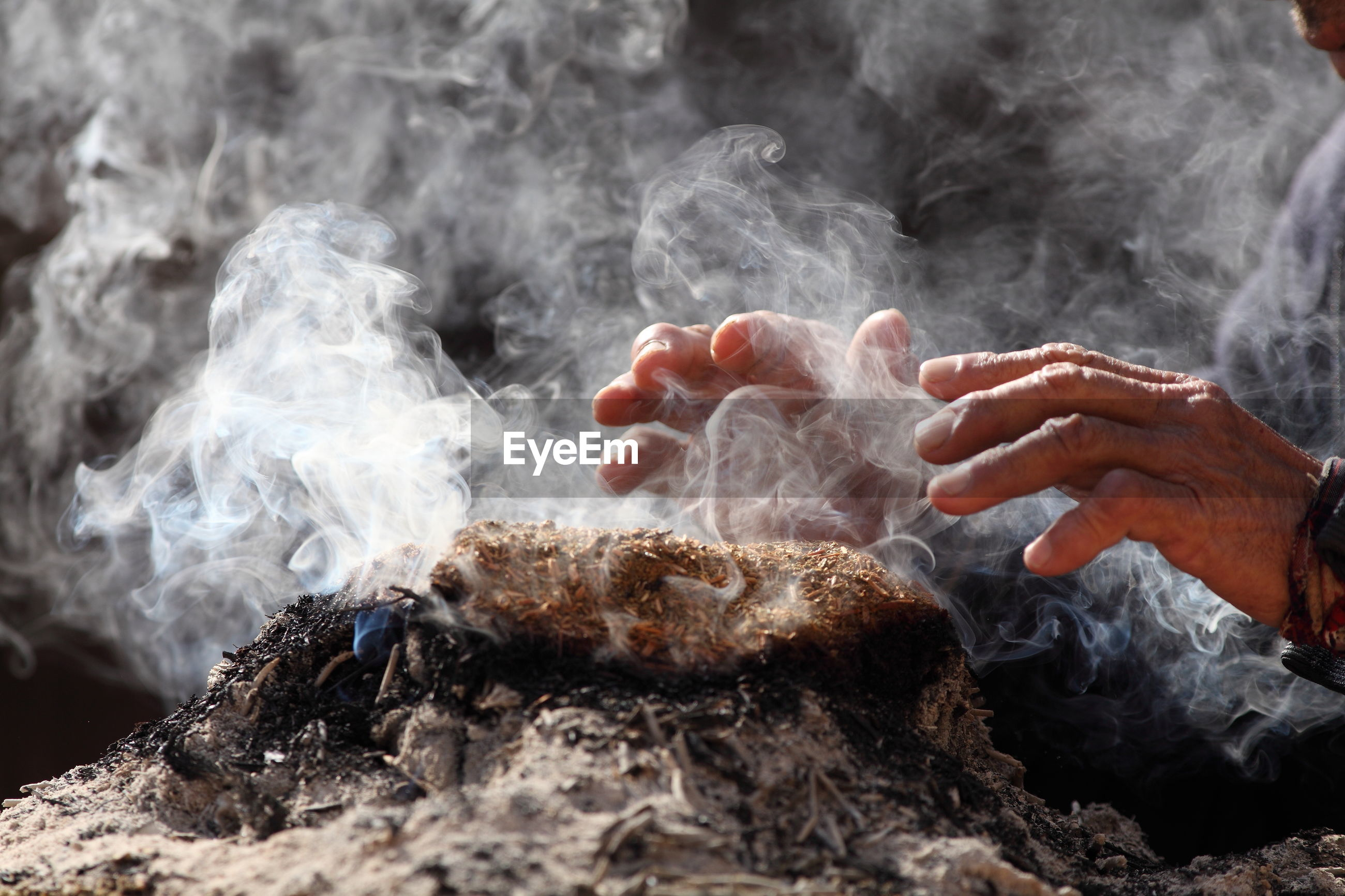Cropped image of hand over smoke emitting from incense at temple