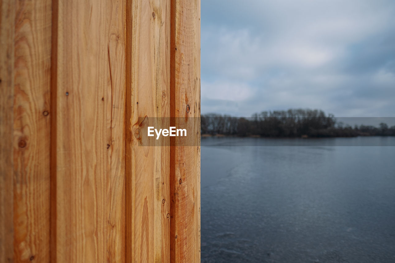 CLOSE-UP OF WOODEN POST AGAINST LAKE