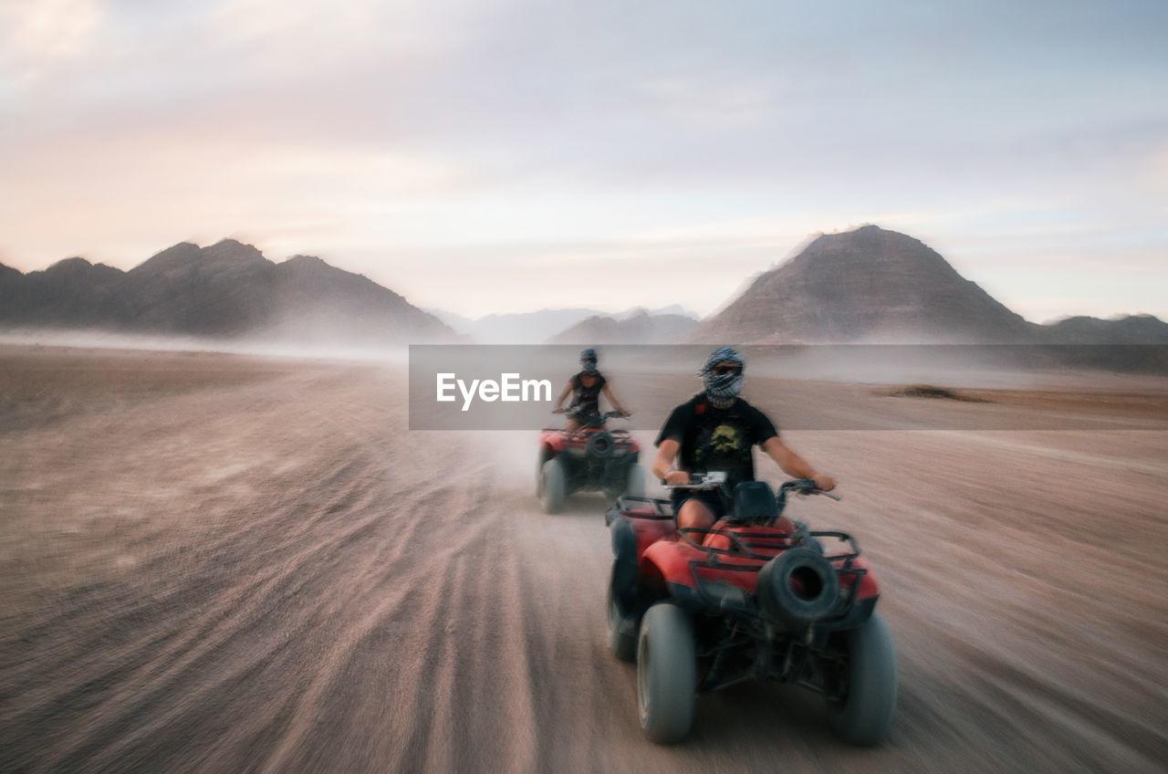 Friends Riding Quadbikes At Desert Against Sky During Sunset