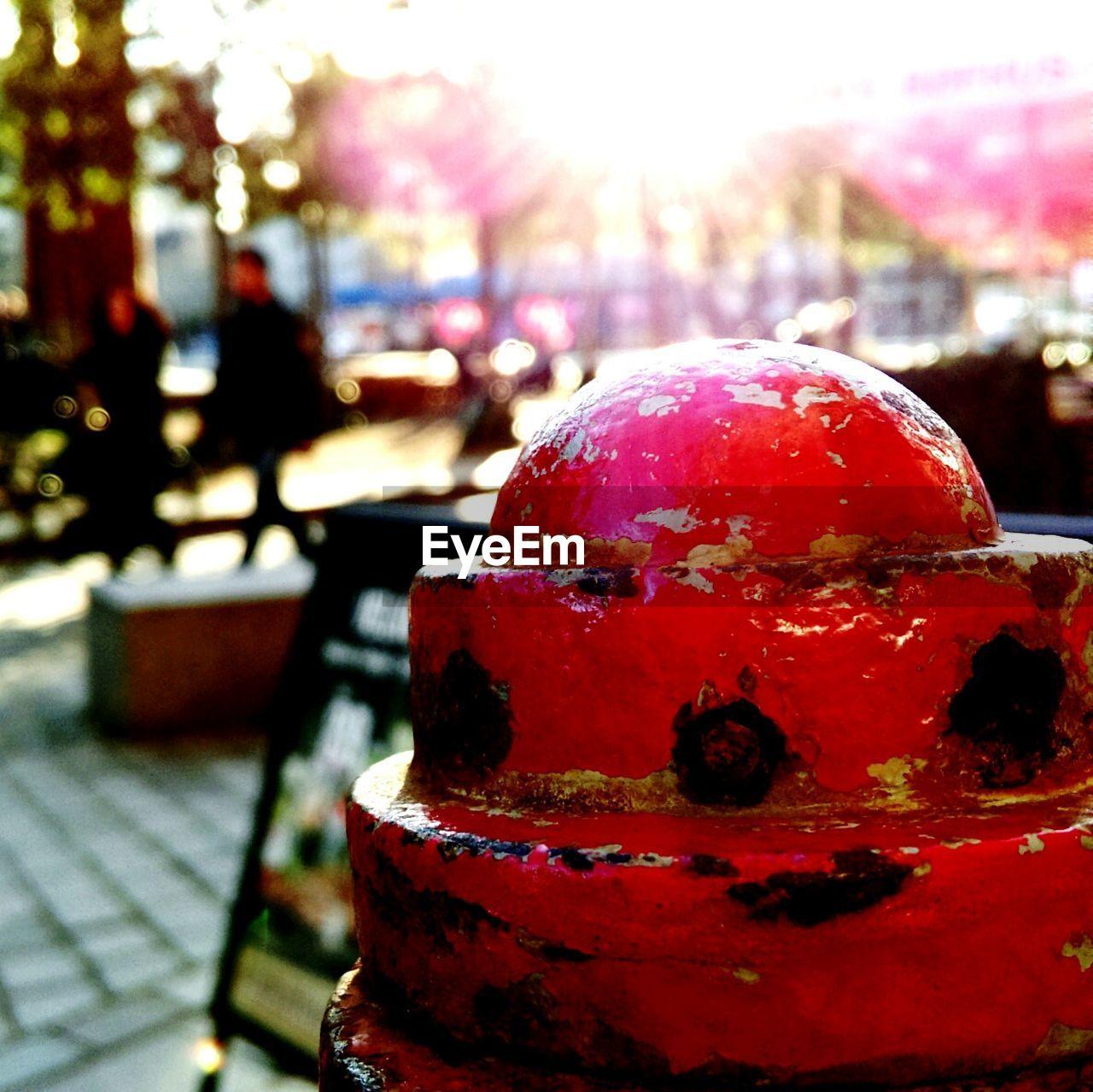Metallic red bollard on footpath in city