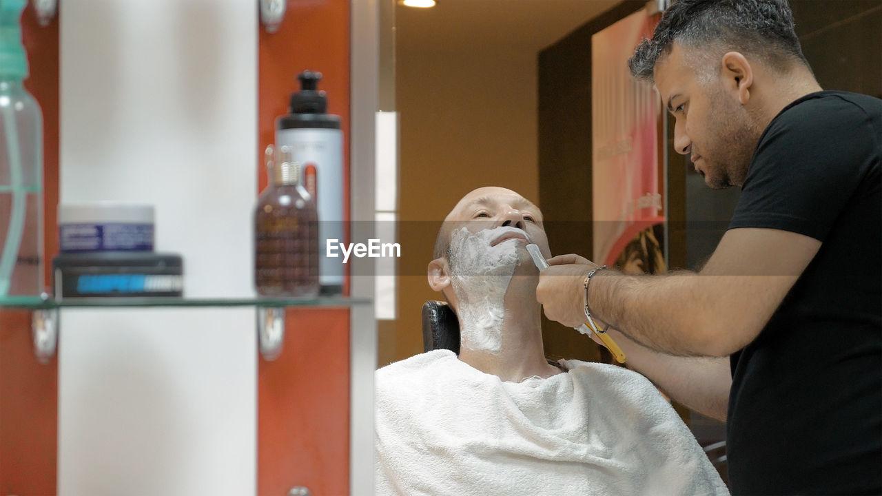 Barber Doing Shaving Of Mature Man In Salon