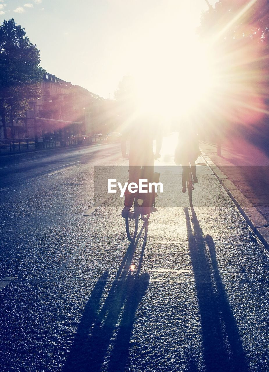 Rear view of two people bicycling on road against sunlight