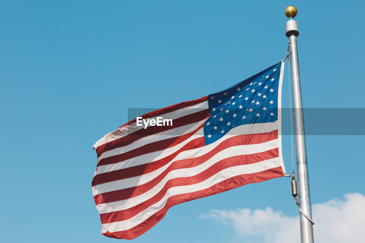 Low angle view of american flag fluttering against blue sky