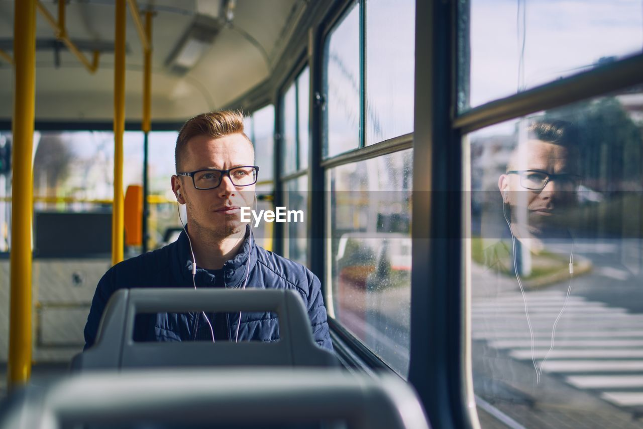 real people, mode of transportation, transportation, glass - material, young adult, transparent, land vehicle, glasses, eyeglasses, vehicle interior, young men, one person, portrait, front view, window, public transportation, males, casual clothing, outdoors