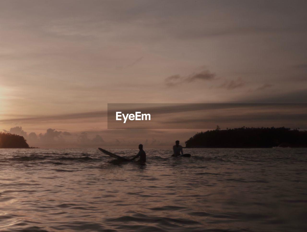 Men surfing in sea during sunset