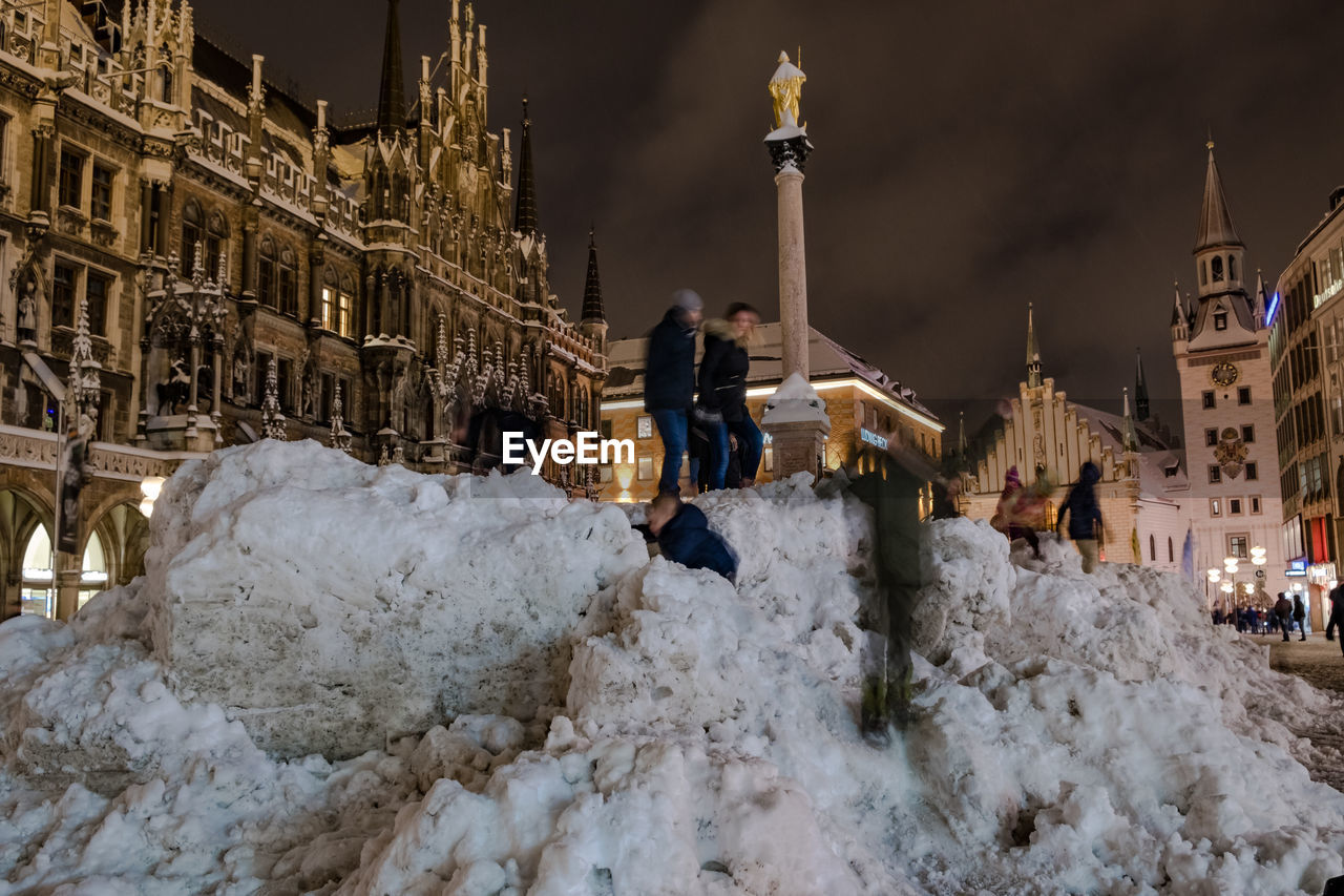 PEOPLE ON SNOW IN CITY AT NIGHT