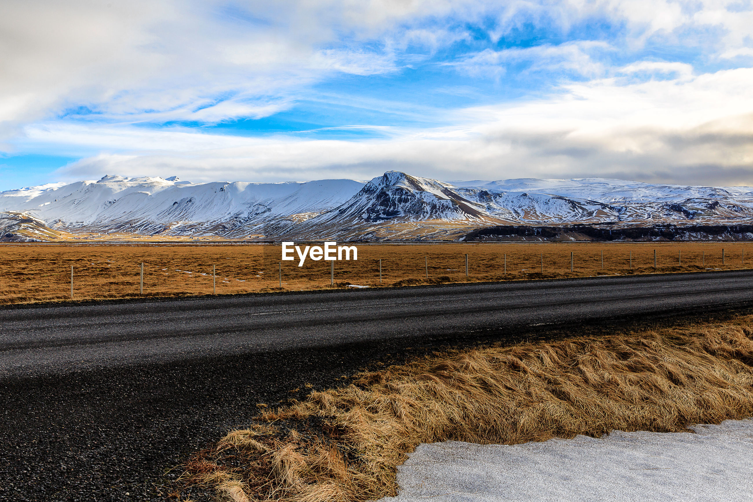 Road amidst field against snowcapped mountains