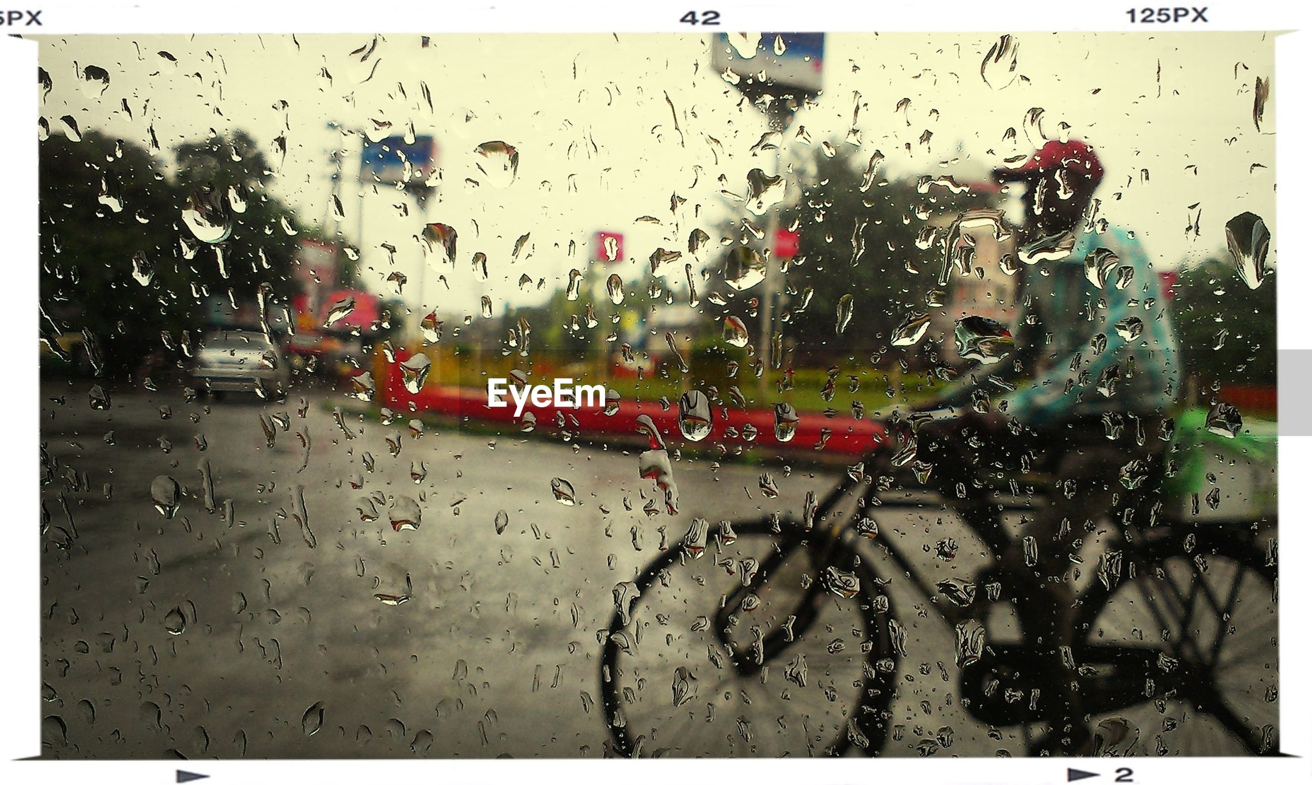 View of man cycling across waterdrops on glass
