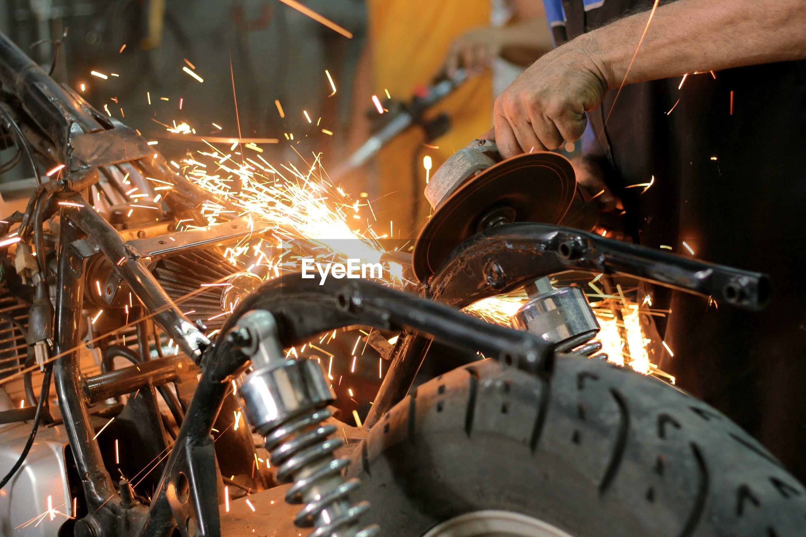 Cropped hand welding parts in motorcycle repair workshop