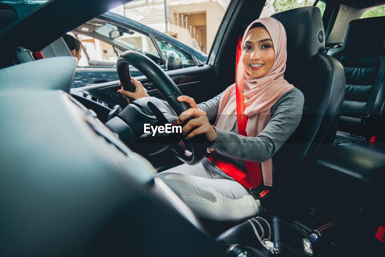 Portrait of female driver sitting in car
