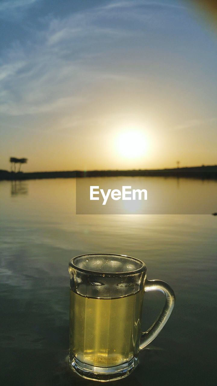 Drink in glass at lakeshore against sky during sunset