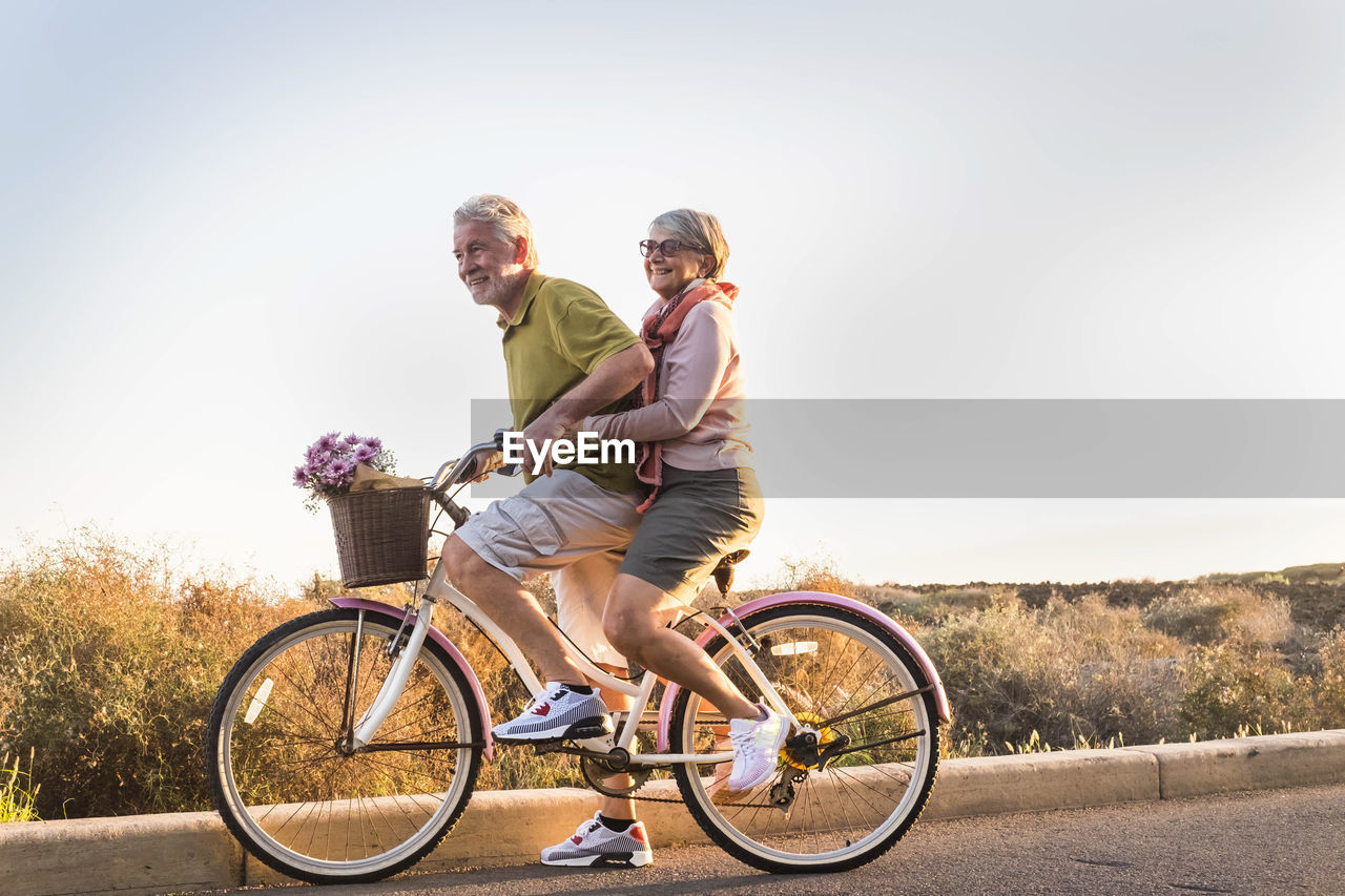 Couple Riding Bicycle On Road Against Sky