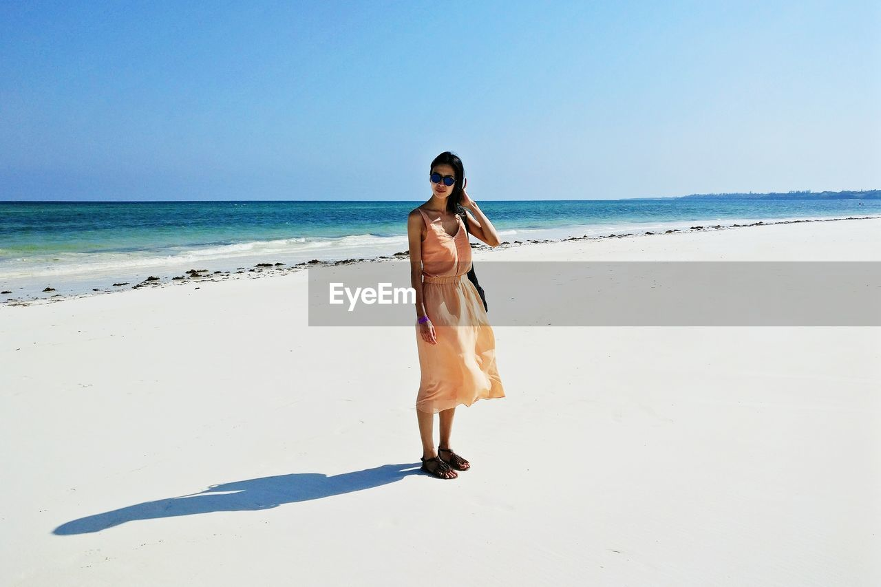 Full Length Of Young Woman Standing On Beach Against Clear Sky