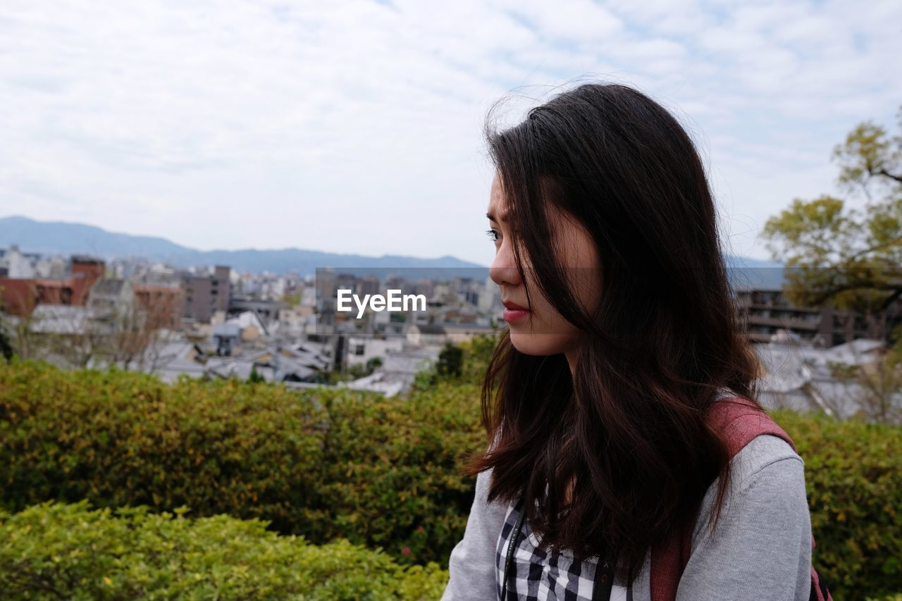 Portrait of beautiful woman standing against cityscape