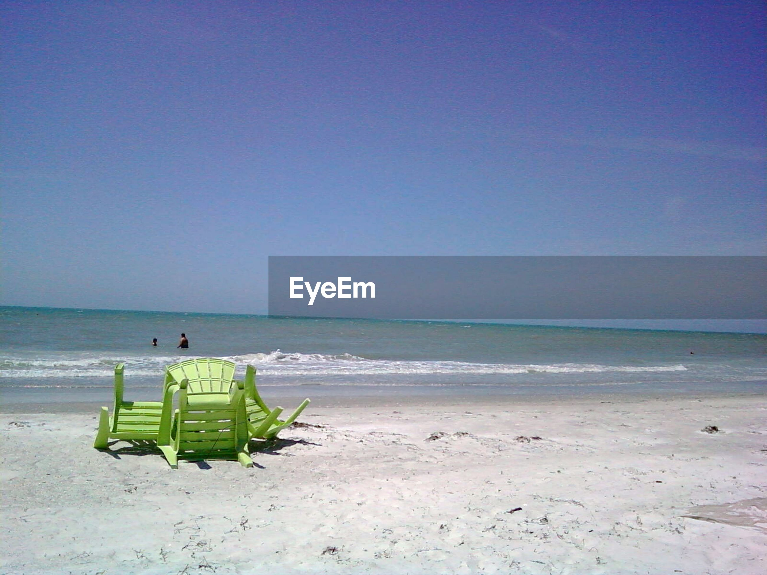 Green Chairs On Beach Against Sky