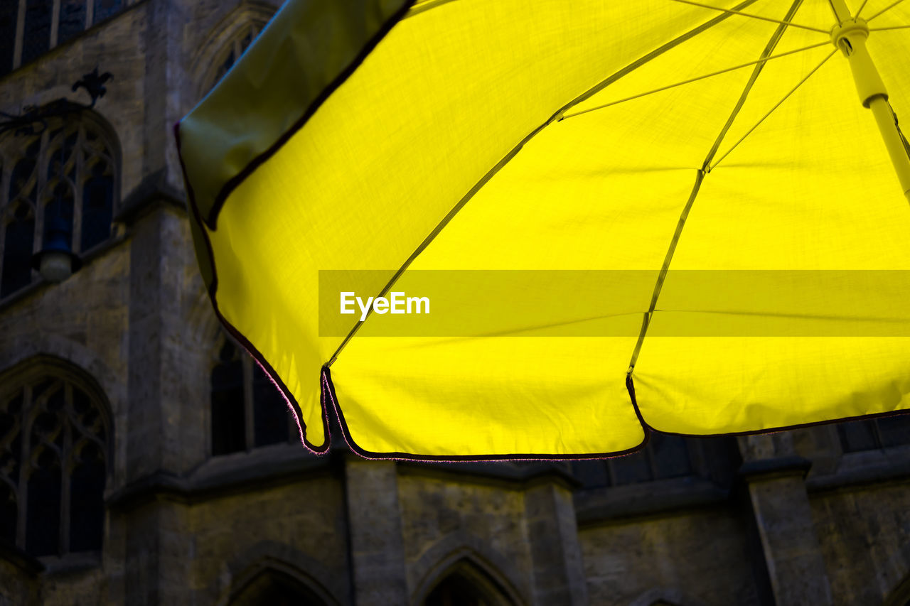 yellow, built structure, architecture, no people, protection, building exterior, low angle view, day, umbrella, textile, pattern, security, outdoors, focus on foreground, close-up, arch, the past, nature, history