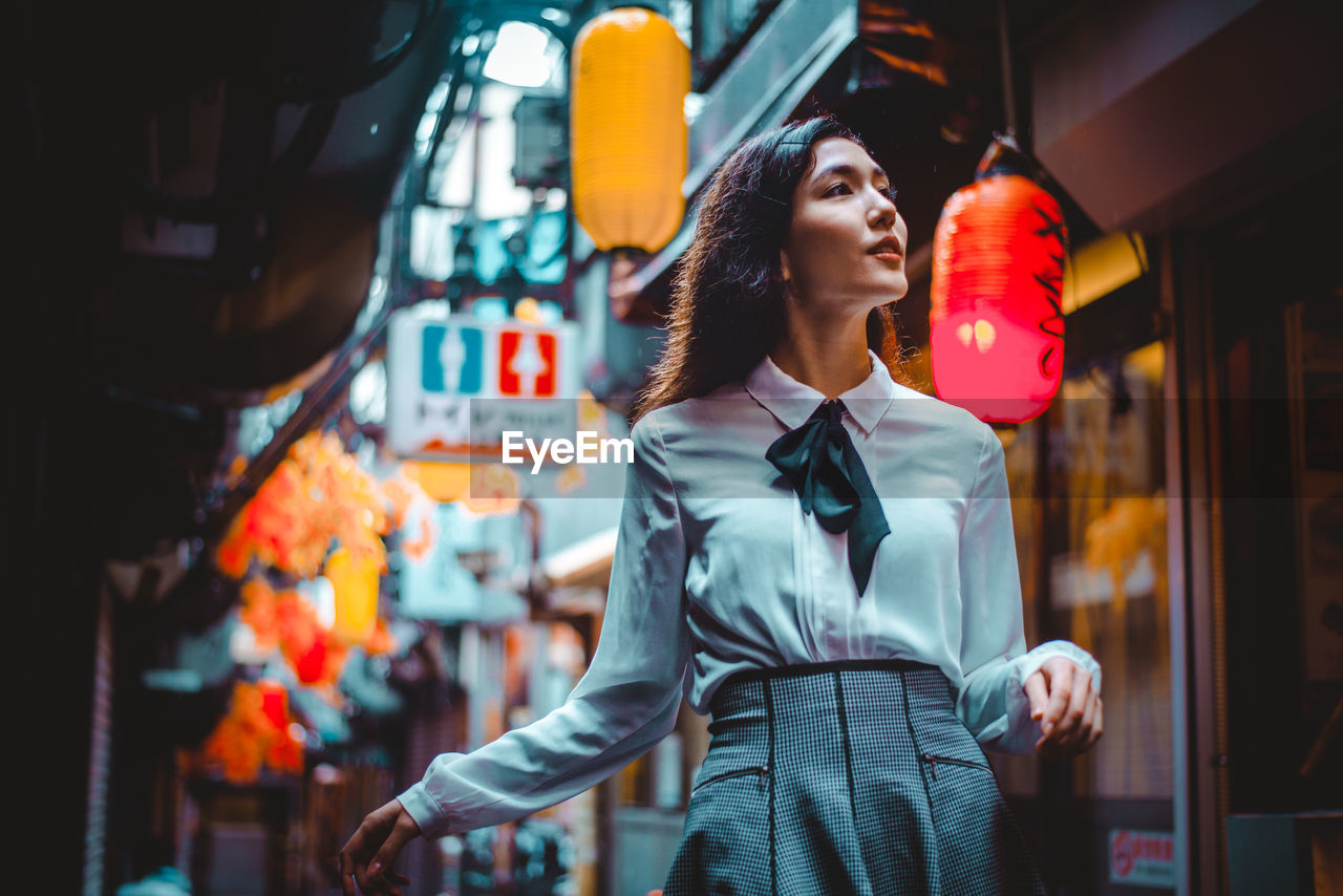 FULL LENGTH OF YOUNG WOMAN LOOKING AT CITY