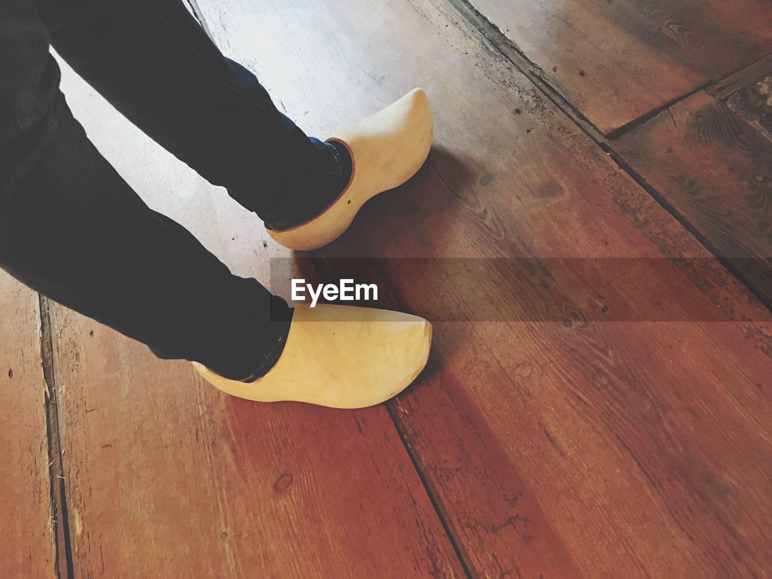 Low section of man wearing clogs while standing on hardwood floor