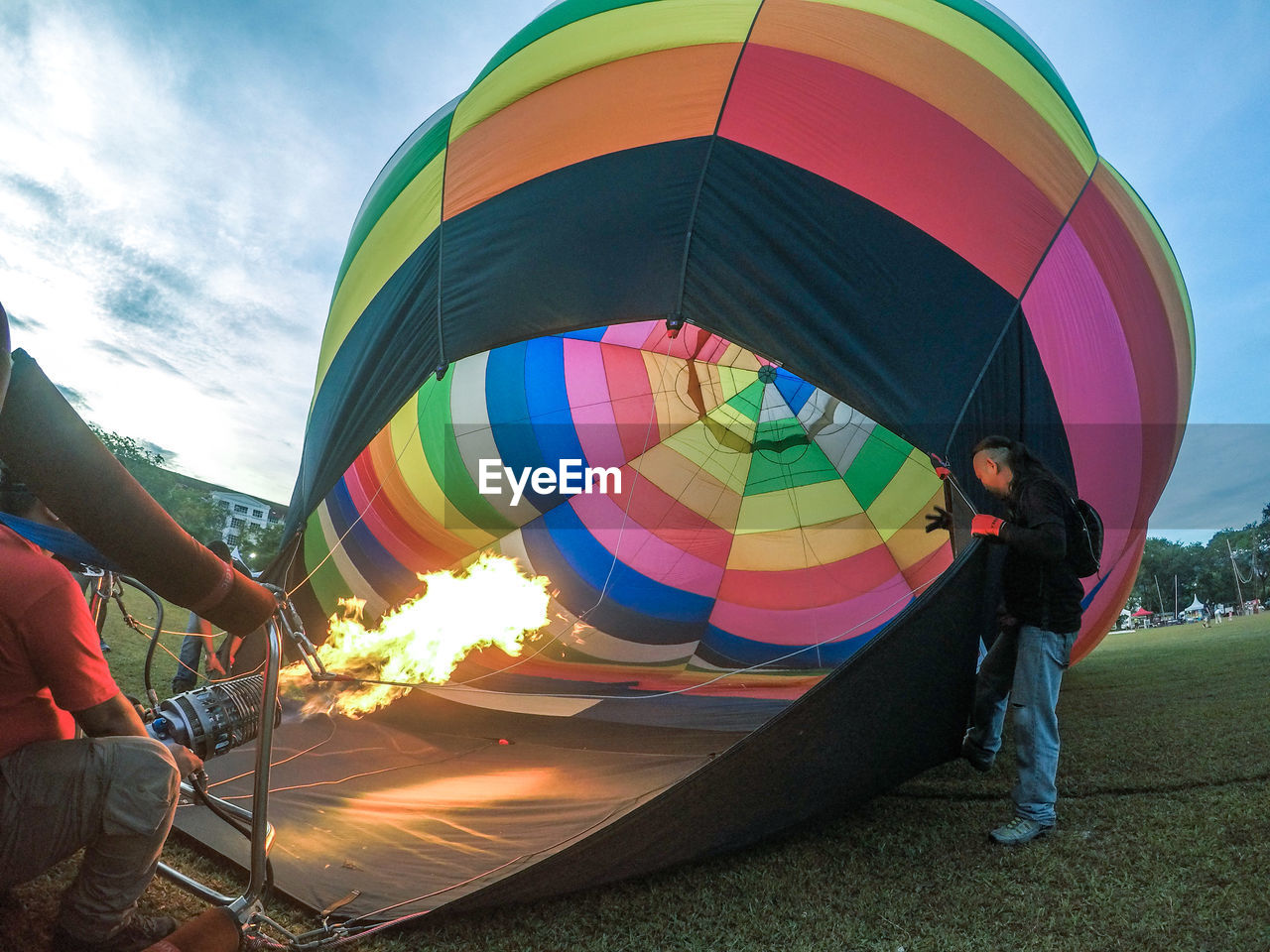 real people, men, multi colored, leisure activity, people, nature, fire, burning, lifestyles, adventure, two people, flame, fire - natural phenomenon, sky, heat - temperature, motion, holding, day, outdoors, inflating