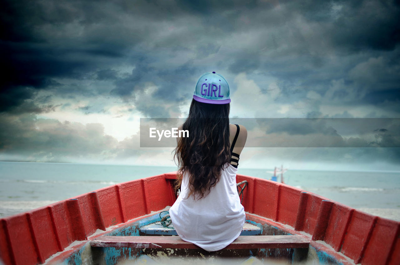 Rear view of woman sitting in boat on sea against cloudy sky
