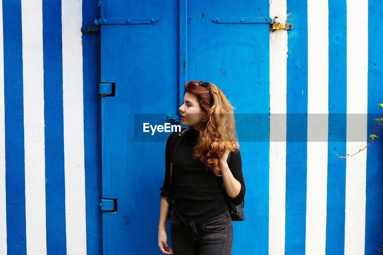 Young Woman Standing Against Blue Door