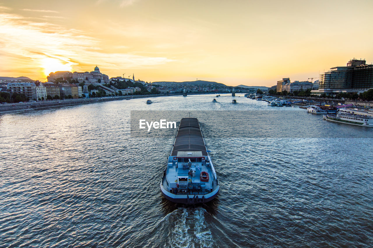 BOAT SAILING ON RIVER AGAINST SKY DURING SUNSET