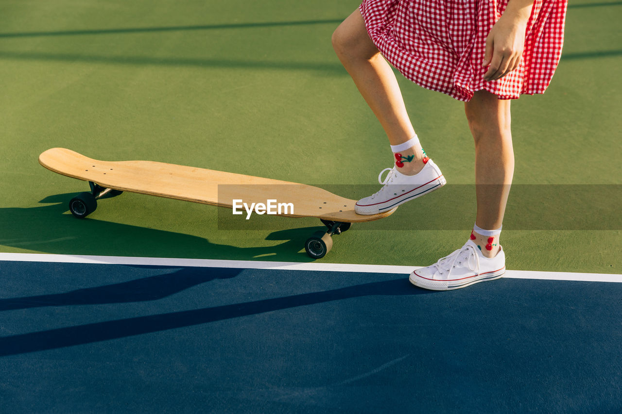 Girl in dress with foot on skateboard on a tennis court