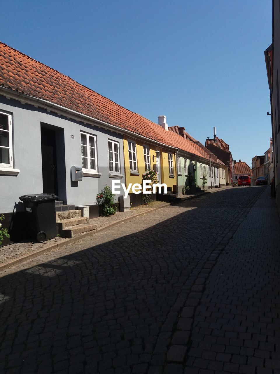 building exterior, built structure, architecture, building, sky, clear sky, city, street, sunlight, nature, copy space, cobblestone, house, residential district, day, no people, window, outdoors, roof, blue, paving stone, roof tile