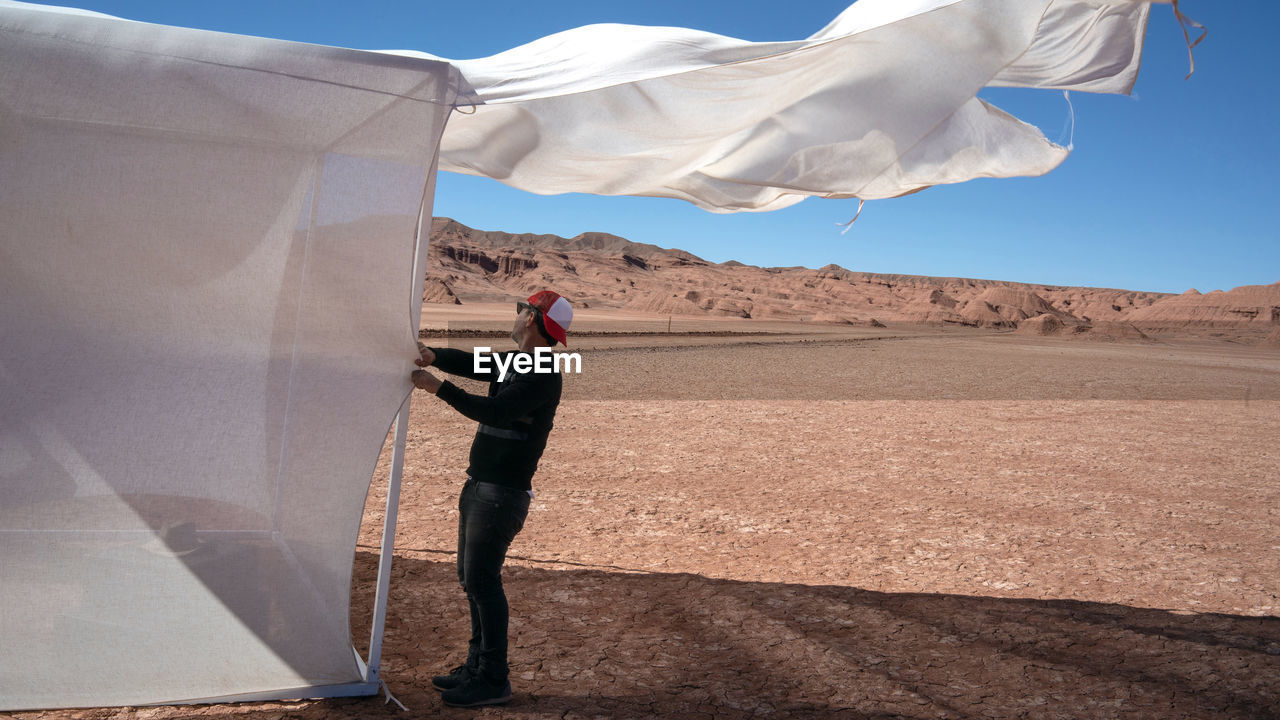 Side view of man standing by tent