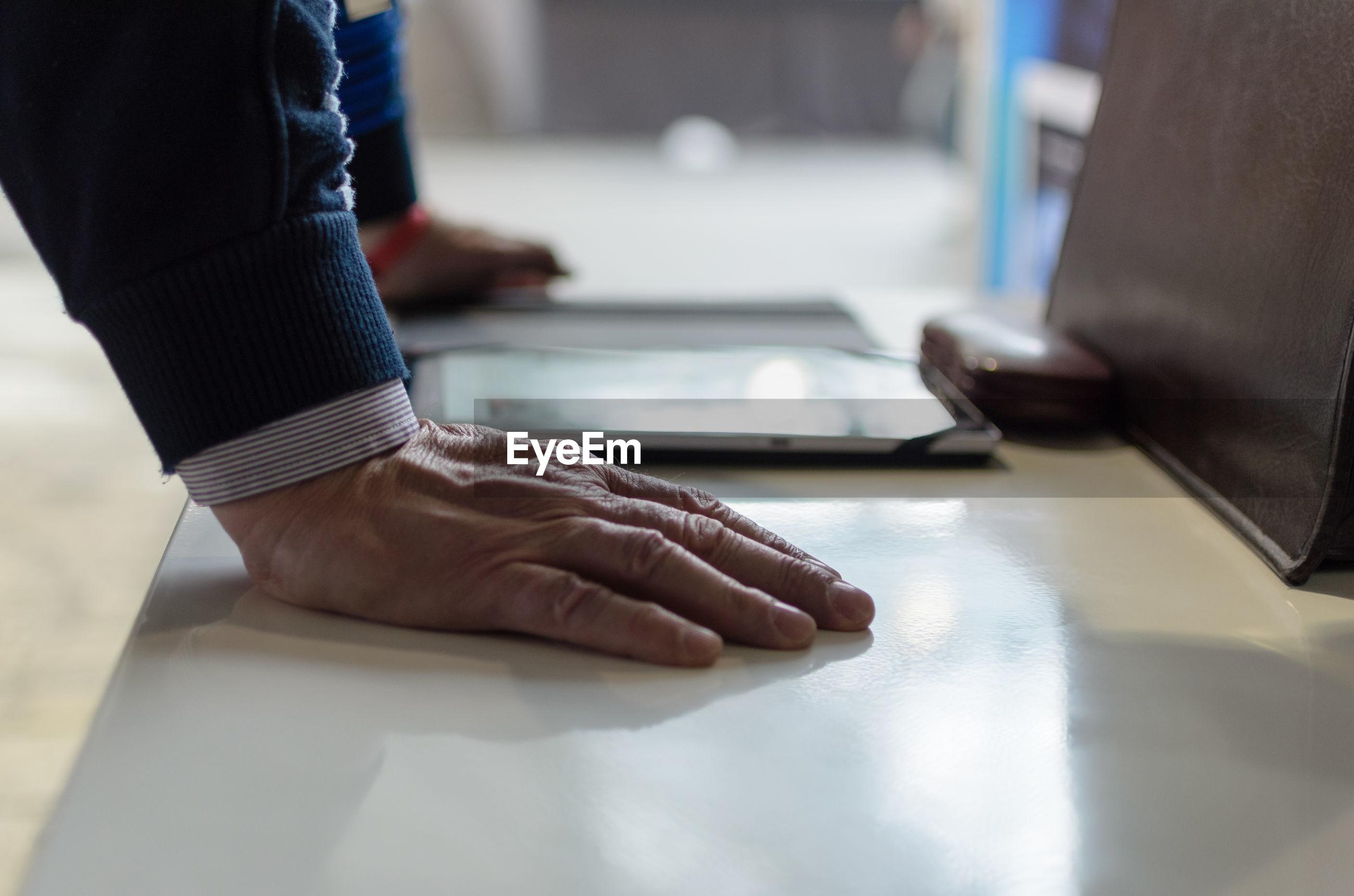 Cropped hands of businessman using digital tablet at desk
