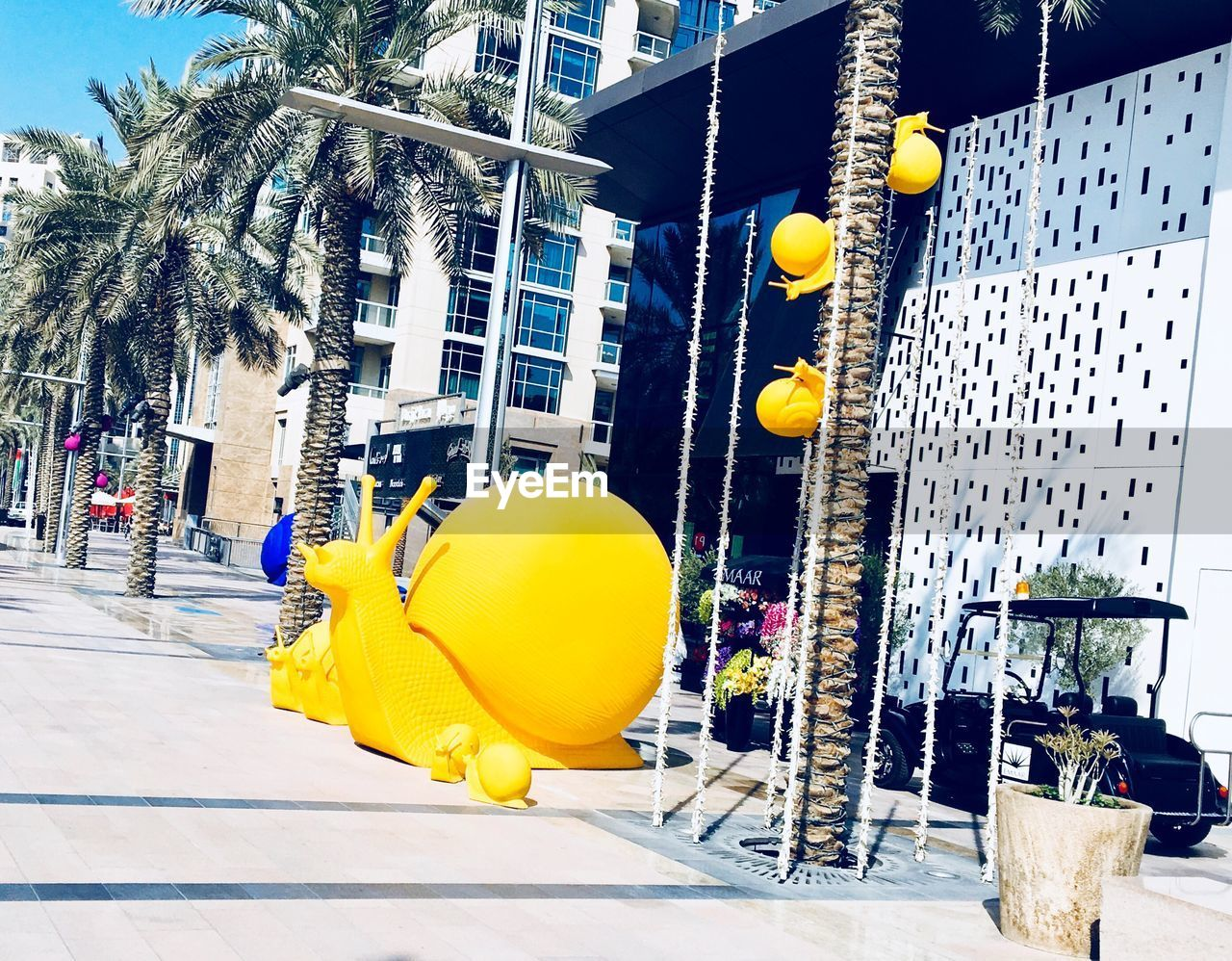 building exterior, balloon, yellow, tree, built structure, outdoors, architecture, palm tree, day, city, helium balloon, no people