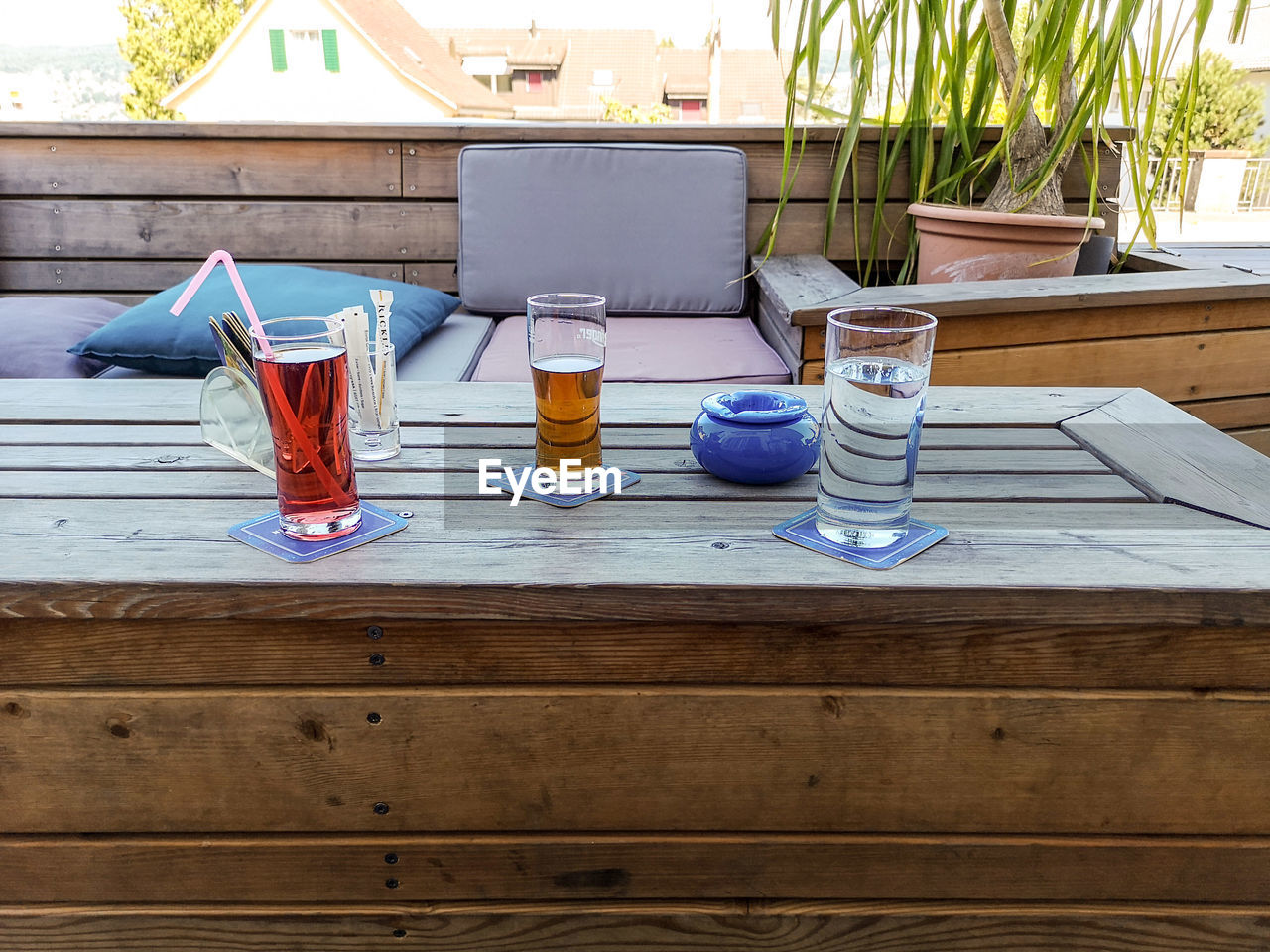 table, wood - material, drink, drinking glass, no people, glass, household equipment, refreshment, food and drink, day, container, still life, glass - material, outdoors, absence, bottle, transparent, water, blue