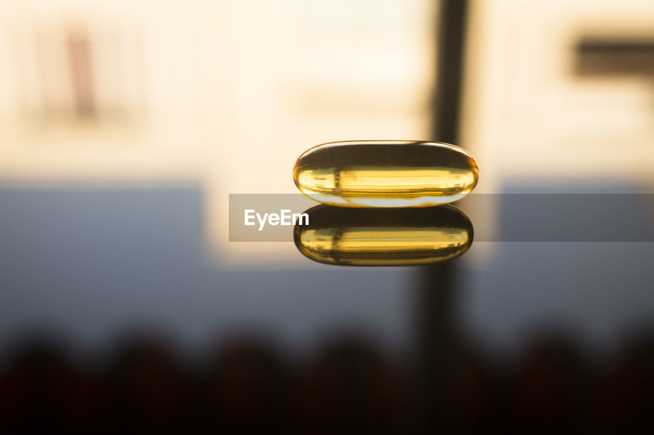 Close-up of pill on table with reflection