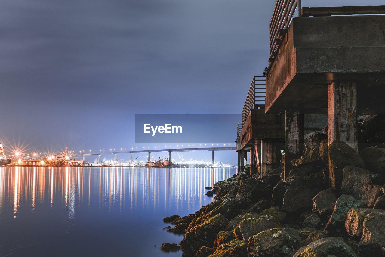 Illuminated Bridge Over Sea Against Sky