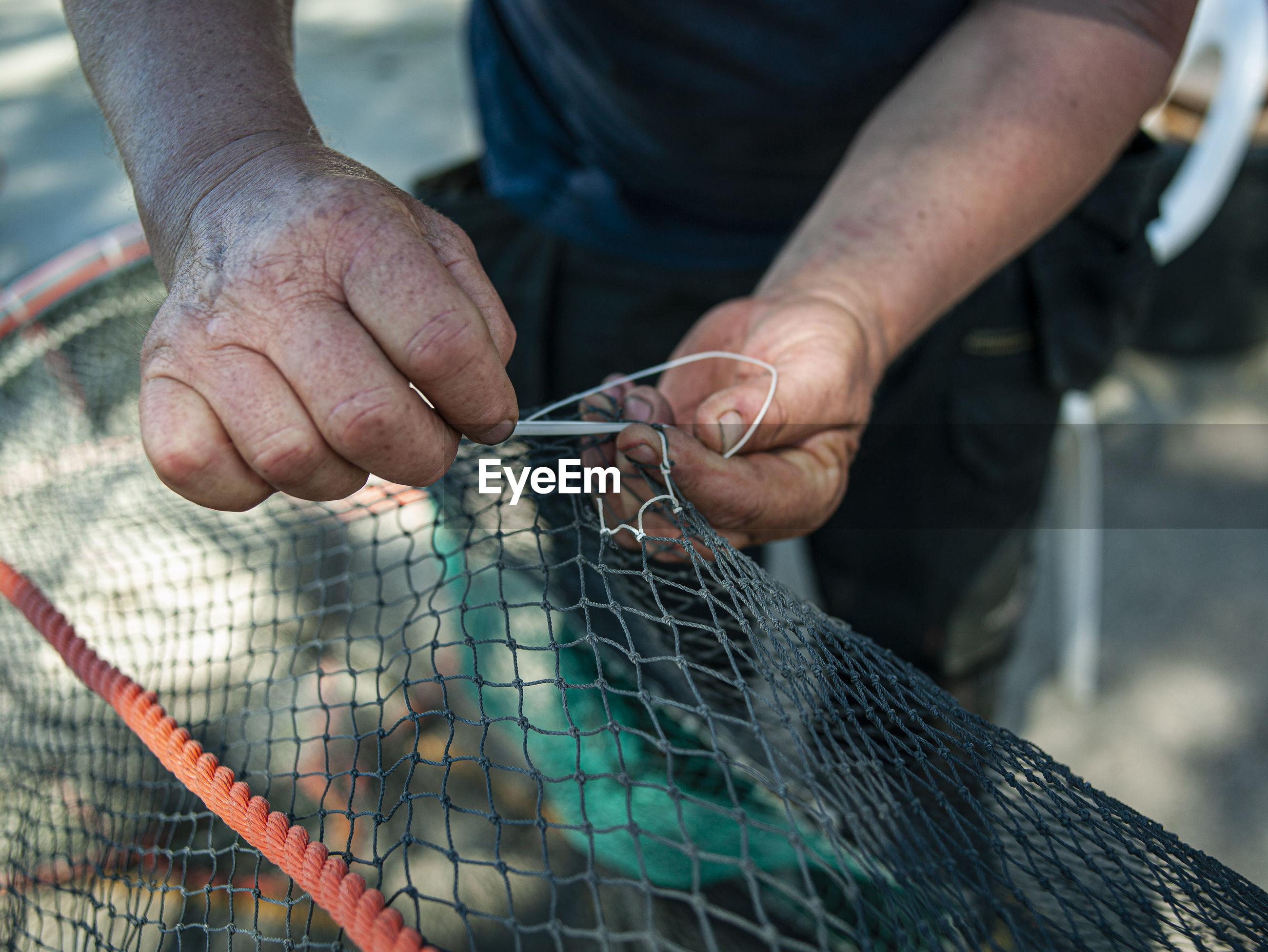 Midsection of man working with fishing net