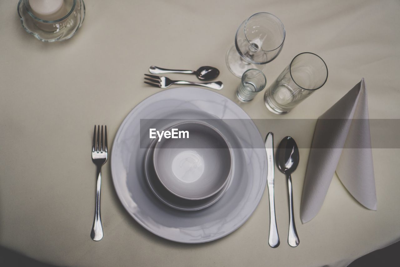table, kitchen utensil, eating utensil, high angle view, plate, indoors, household equipment, spoon, still life, no people, setting, fork, empty, place setting, knife, crockery, table knife, food and drink, drinking glass, glass, silver colored, tray