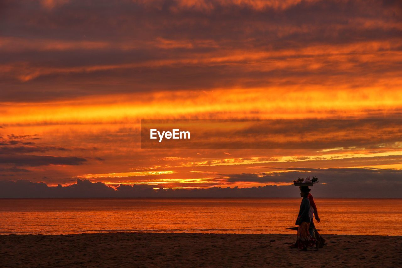 sunset, sky, cloud - sky, orange color, beauty in nature, sea, scenics - nature, water, standing, real people, one person, nature, land, beach, horizon over water, idyllic, lifestyles, tranquility, silhouette, outdoors
