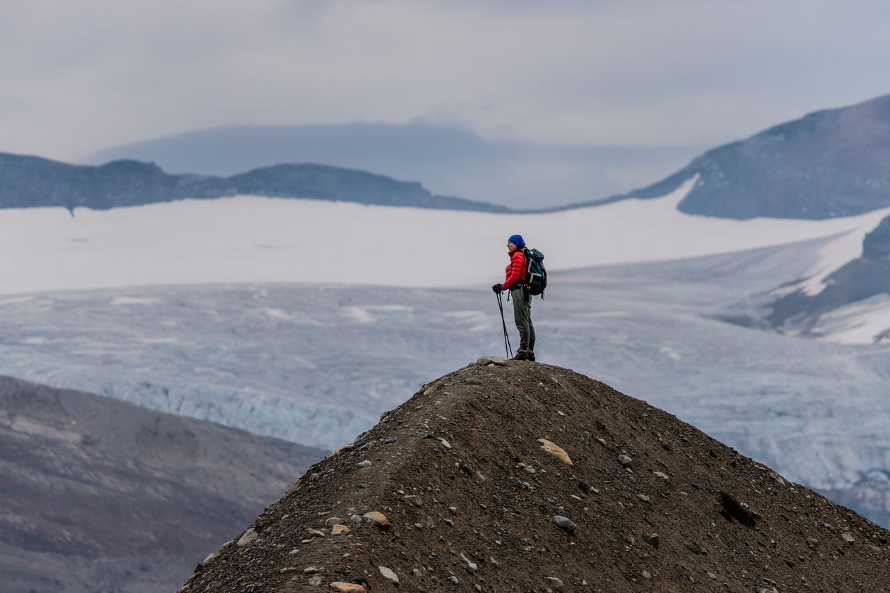 Side View Of Hiker Standing On Mountain Against Sky