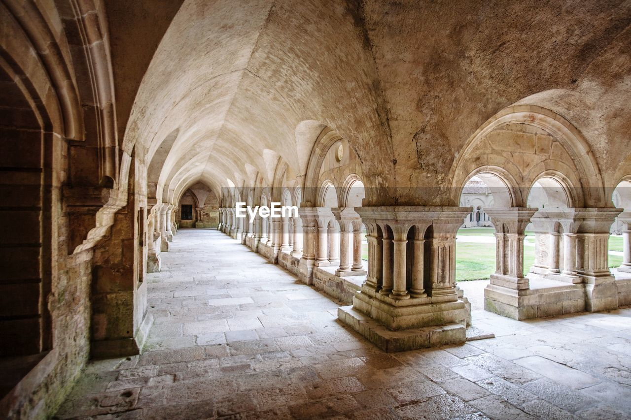 architectural column, architecture, arch, the past, history, arcade, built structure, building, corridor, indoors, travel destinations, old, no people, colonnade, place of worship, religion, day, in a row, ancient, belief, ceiling, abbey, gothic style, ancient civilization, building feature