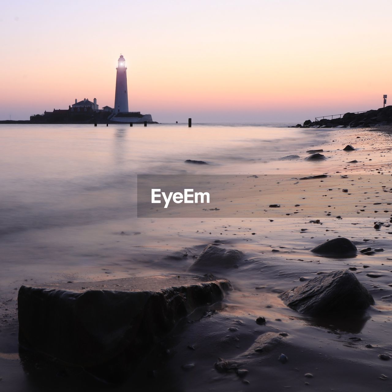 sky, sunset, water, sea, building exterior, land, built structure, beach, beauty in nature, scenics - nature, architecture, nature, tower, orange color, guidance, rock, lighthouse, no people, horizon over water