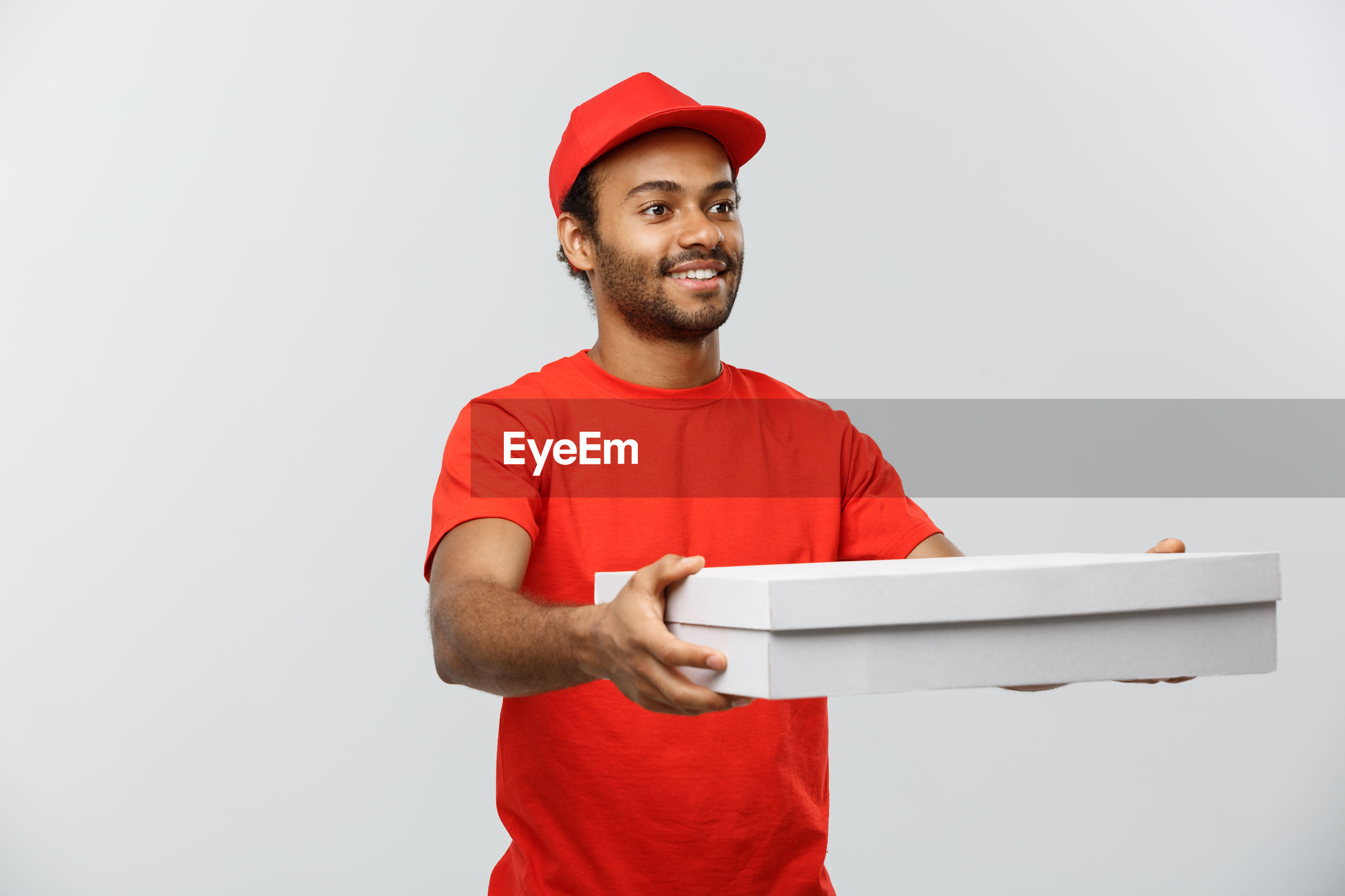 Young delivery man holding cardboard box against white background