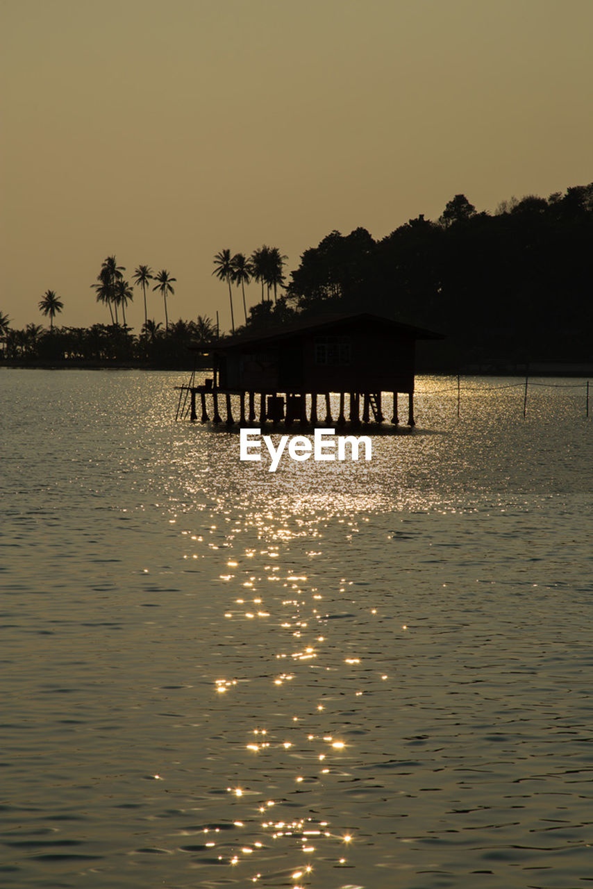 silhouette, water, sunset, waterfront, sea, nature, built structure, outdoors, clear sky, beauty in nature, architecture, sky, no people, day