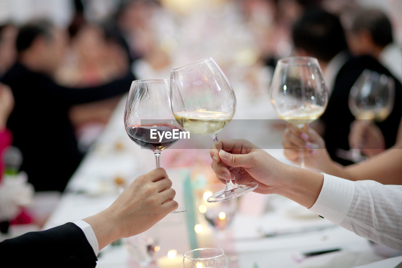 Cropped Image Of Business People Toasting Wineglasses At Dining Table