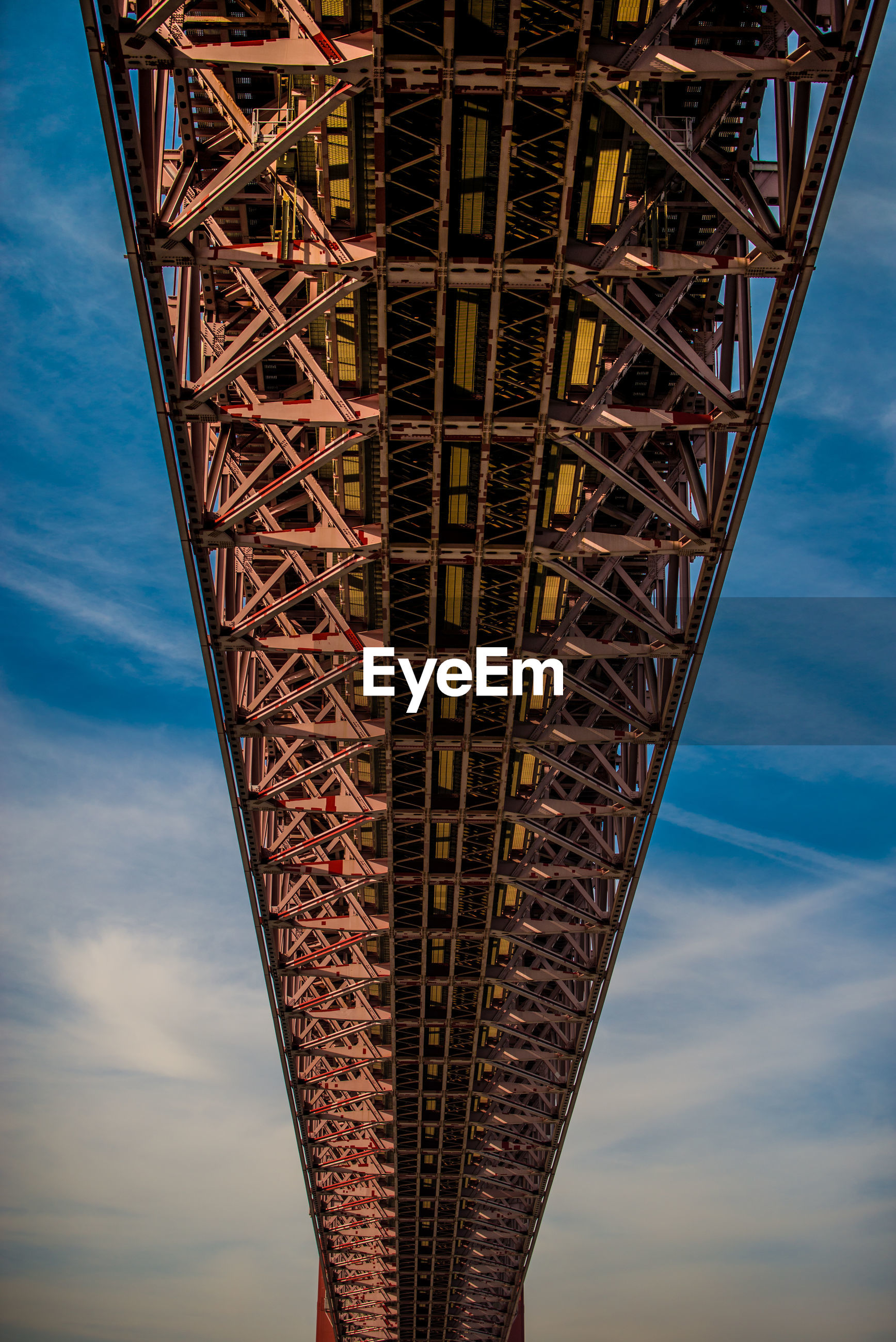 LOW ANGLE VIEW OF BRIDGE TOWER AGAINST CLOUDY SKY