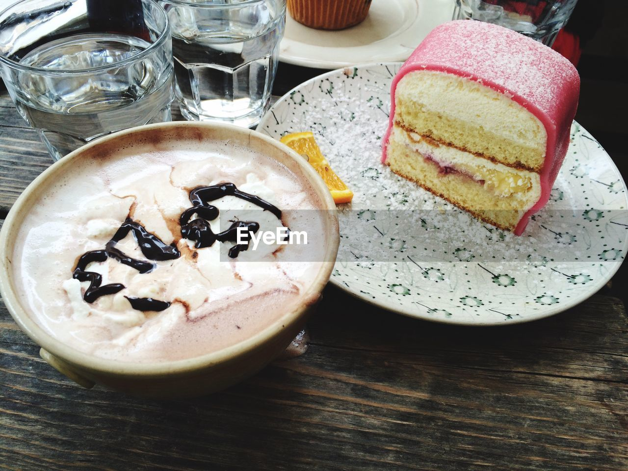 High angle view of coffee and cake slice on wooden table