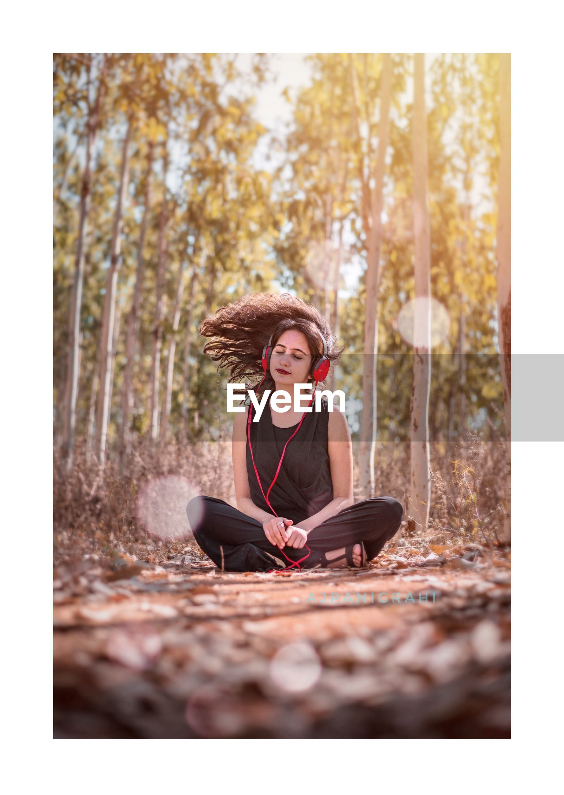 Woman with tousled hair listening to music while sitting against trees in forest